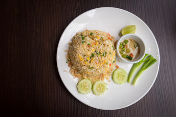 Crab meat fried rice with vegetables in dish on wooden table