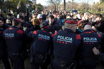 Pro-independence demonstrators are held back by police as they try to make their way toward the regional parliament in Barcelona