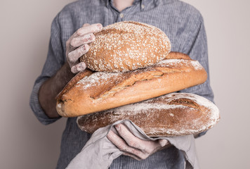 Pile of rustic crusty breads in baker man's hands