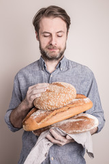 Baker man holding pile of rustic crusty breads
