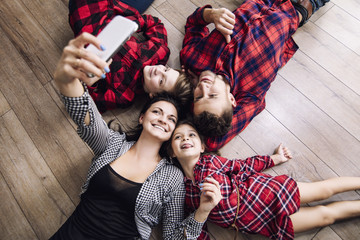 Happy beautiful family happy making selfie on mobile phone together at home lying floor top view