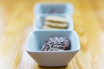 Close up of a bowl of cookies on an old wooden table. Shallow depth of focus.