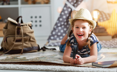 funny child girl tourist with world map, backpack and magnifier