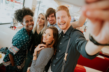Group of young people taking selfie with mobile phone
