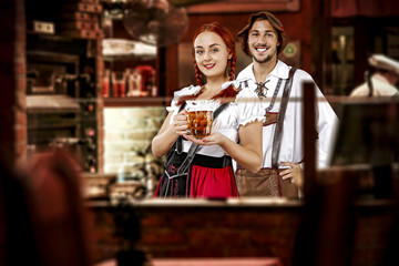 young two people in bavarian clothes and small business of bar .