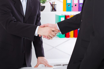 Business deal. Partnership meeting concept with successful businessmen handshaking at office background. Selective focus, copy space and horizontal