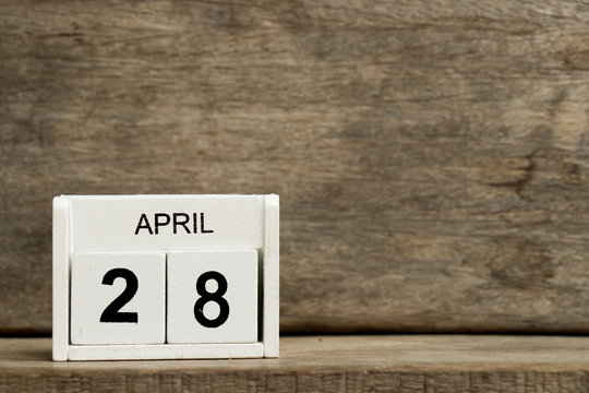 White block calendar present date 28 and month April on wood background
