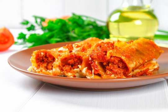 Traditional Italian pasta cannelloni. Baked tubes stuffed with minced meat with parmesan cheese and bechamel sauce on a white wooden table.