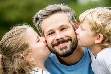 Vater wird von seinen Kindern geküsst