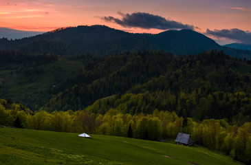 grassy rural slope at dusk. woodshed on the hillside near the forest. beautiful landscape with reddish sky and rolling hills in springtime