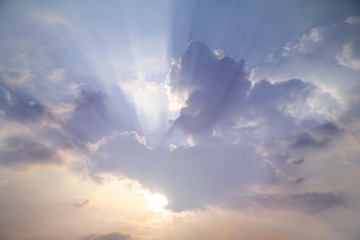Sun shines through white clouds caused rays of light on hazy day blue sky