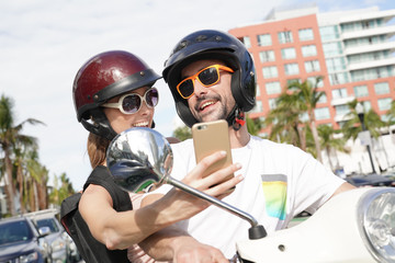 Girl riding scooter with boyfriend and taking picture with smartphone