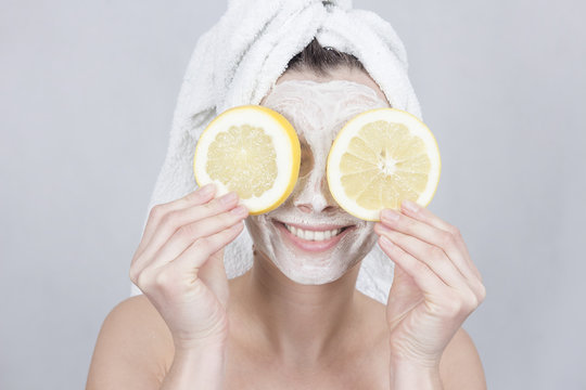 Smiling brunette woman holding two slice of lemon in front of her face. woman with moisturizing facial mask. Beauty and skin care concept.