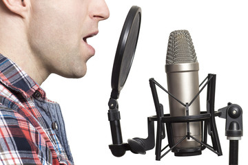 Record voice to microphone in studio. young man sings in studio condenser microphone with spider isolated on white background. Write song in sound recording studio.