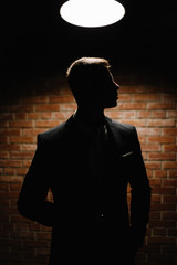 Handsome young brunette model, wearing in black and white suit,