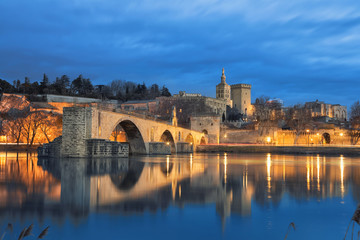 View on Pont d'Avignon 12th century bridge and city skyline reflecting in water at dusk in Avignon, Provence, France