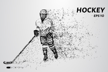 Hockey player slides on the ice with the puck. Hockey consists of particles.