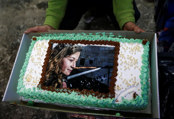 A man displays a cake with the picture of Palestinian teen Ahed Tamimi, who is detained by Israel, during a symbolic birthday party for Tamimi in the West Bank city of Hebron