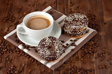 Cup of coffee with milk   and chocolate donut on a wooden table