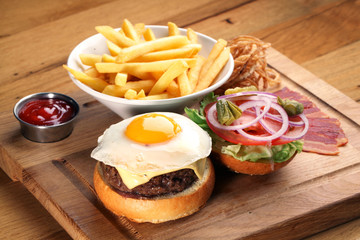 Burger with beef steak and fried egg.