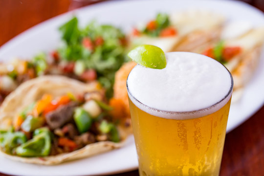 Cold beer with lime wedge and Mexican food dish in beef tacos in background.