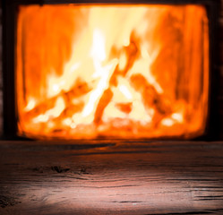 Wooden table top and burning warm fire at the background.