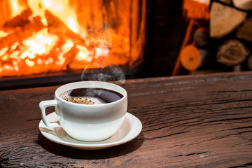 Cup of hot coffee on the wooden table and fireplace at the background.