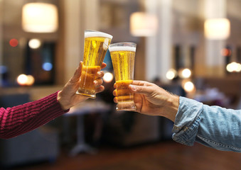Beer glasses raised in a toast. Close-up hands with glasses.