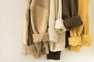 Maxi knitted sweater in warm natural colors hanging on the crutch on the wall, space for text.Cozy rustic fashion concept, everyday clothes, comfortable oufit in natural colors Wall mural