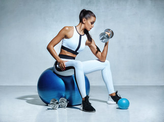 Strong woman working out with dumbbells sitting on gymnastic ball. Photo of sporty latin woman in sportswear on grey background. Sports