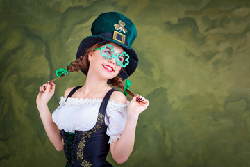 A girl in a St. Patrick costume is smiling on a green background.