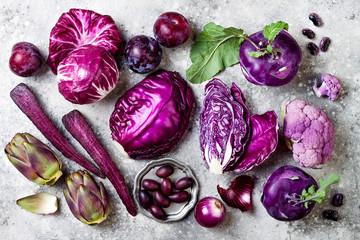 Raw purple vegetables over gray concrete background. Cabbage, radicchio salad, olives, kohlrabi,...