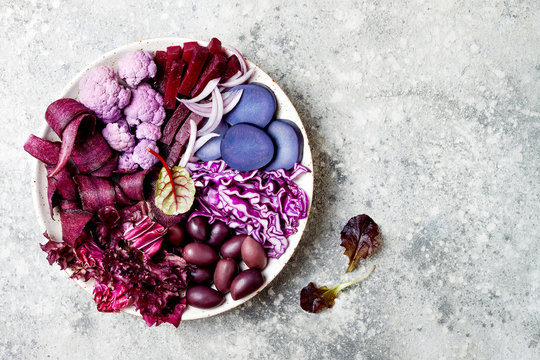 Purple Buddha bowl with spiral carrots, cauliflower, beet, onion, potato, shredded red cabbage, radicchio salad, kalamata olives. Vegan detox veggie bowl