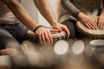 Close up of hands on african drums, drumming for a music therapy Wall mural
