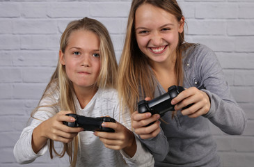 Two sisters kids playing video games at home together. Happy childeren, carefree childhood concept