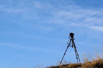 Camera on a tripod against a blue sky