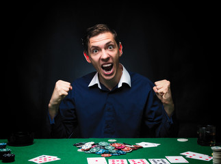Man is playing poker. Emotional  card player win in game, man very happy with making right choices, winning all the chips on bank. Concept of victory