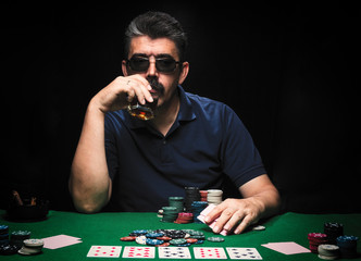 Man is playing poker. drink whiskey, man holds cards on table, winning all the chips on bank. Concept of victory