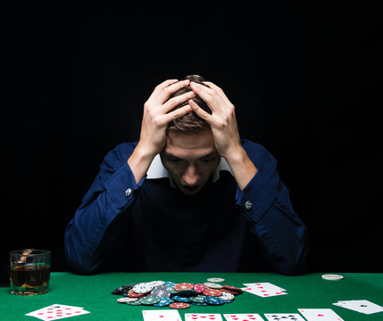 Man is playing poker. Emotional fail in game, game over for card player, man very angry with foolish choices, loosing all the chips on bank. Concept of victory and loosing