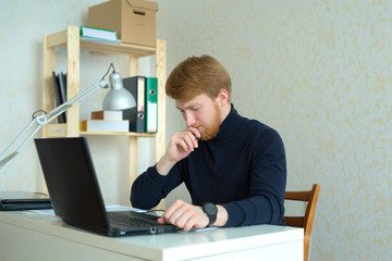 handsome young man with a red beard working in his office behind a laptop