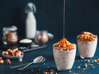 Gingerbread coconut overnight oatmeal served with granola,pecan,honey.Recipe and idea healthy vegan breakfast - plant-based milk overnight oats with chia and gingerbread spices cinnamon, nutmeg,ginger