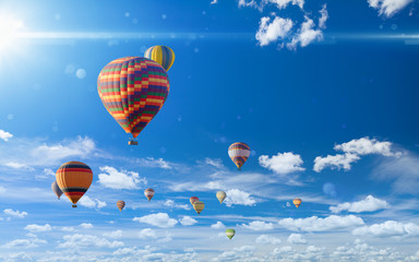 Foto auf AluDibond Ballon Colorful hot air balloons flying in blue sky with white clouds and bright sun light