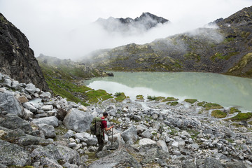 Hiker descending toward green glacial lake in Hatcher Pass area of Alaska