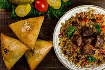 Uzbek national dish of pilaf and samsa on a dark wooden background with pickles