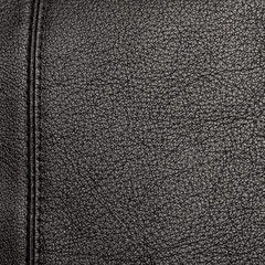The texture of the two stitched halves of soft black leather with a neat stitch