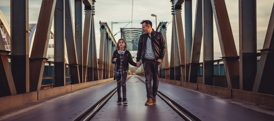 Father and daughter walking across the freight bridge