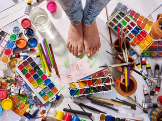 Authentic paint brushes still life on floor in art class school. Group of brush in clay jar. Barefooted female feet among creative mess.