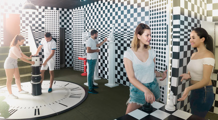 Five adults solving different conundrum in quest room