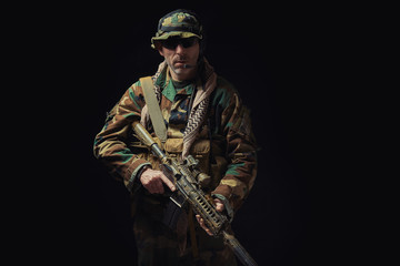 soldier of the American special forces in Afghanistan poses with a rifle on a black background