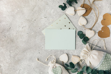 Workspace. Wedding invitation card and eucalyptus leaves on white background. Overhead view. Flat lay, top view wedding invitation card Templates